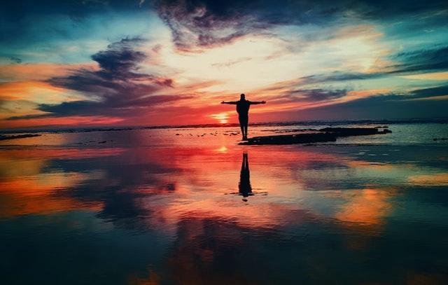 両手を広げて海辺に立っている男性
